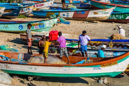 untangle: Children help fisherman untangle a network, Kanyakumari, Tamil Nadu, India Editorial