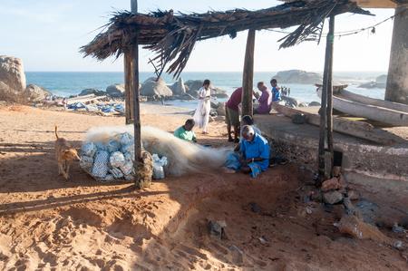 untangle: People help fisherman untangle a network, Kanyakumari, Tamil Nadu, India