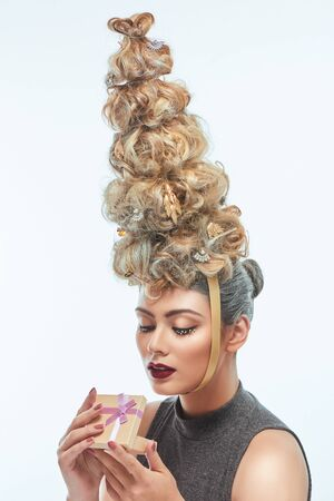 The beautiful woman with Christmas tree hairstyle, snow on eyelashes and little gift box