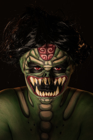 succubus: Professional body art of scary green monster snake with grin and red eyes