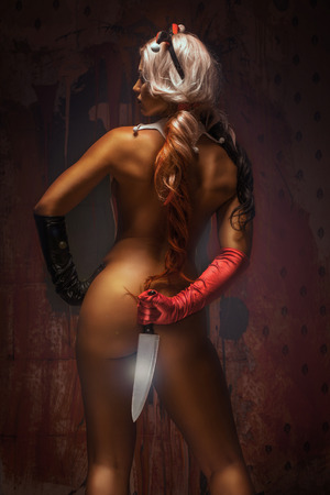 Sexy blonde harlequin woman with knife on dark background