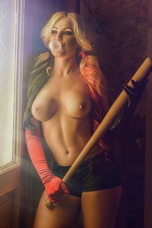 smoking woman: Sexy blonde  woman with batt on dark background Stock Photo