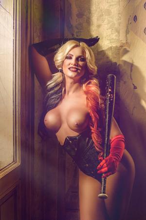 Sexy blonde harlequin woman with batt on dark background