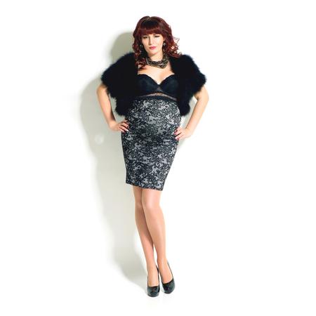 Fashionable redhead pregnant woman in skirt and fur bolero full length