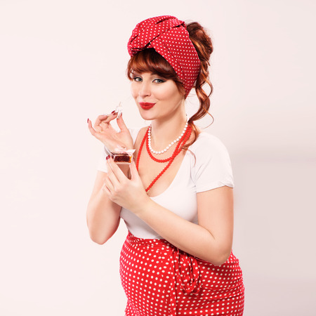 Fashionable redhead pregnant woman in pin up style sniffs perfume Stock Photo