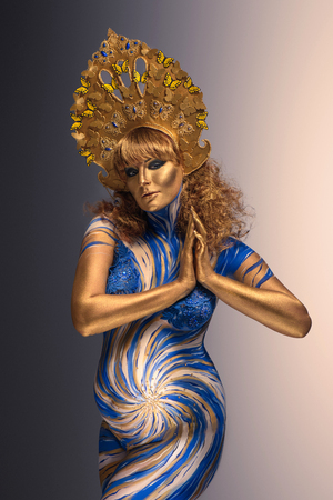 Fashionable redhead pregnant woman with kokoshnik and abstract body art in shades of blue and gold