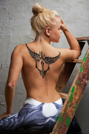 half naked: Blonde half naked girl with black temporary tattoo painted with paints for body art. Stock Photo