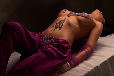 Eastern beautiful brunette woman with mehendi on her stomach Stock Photo