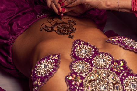 sanskrit: White woman a mehendi artist paints an ornament of henna on an eastern beautiful girl's stomach