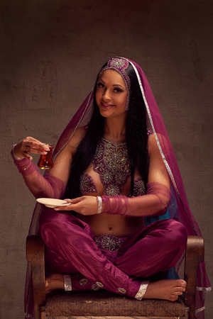 purdah: Eastern beautiful brunette woman in afghani pants, purdah and adornment have a tea armut
