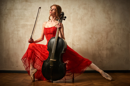 Female ballet dancer in red dress and pointe playing on antique black cello
