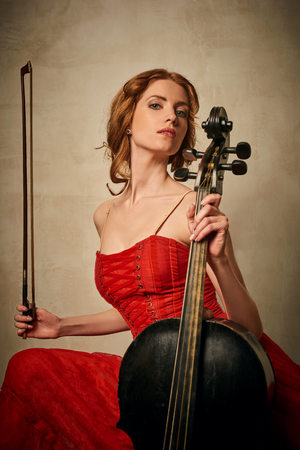 cellos: Female ballet dancer in red dress and pointe playing on antique black cello
