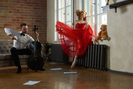 Caucasian handsome cellist visits the muse from fairytale in red dress