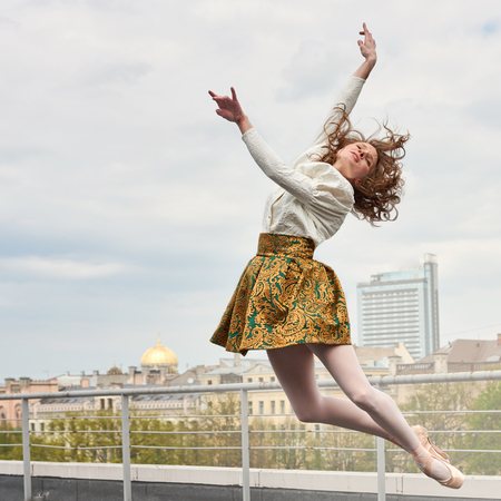 Young caucasian fashion ballerina leaping on the roof