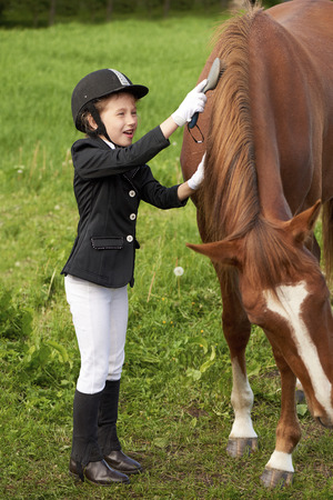razas de personas: Pretty little girl jockey attend and brushing her horse Foto de archivo