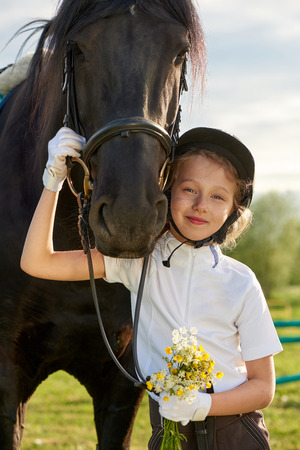 Pretty little girl jockey communicating with her black horse in professional outfit Reklamní fotografie - 81851243
