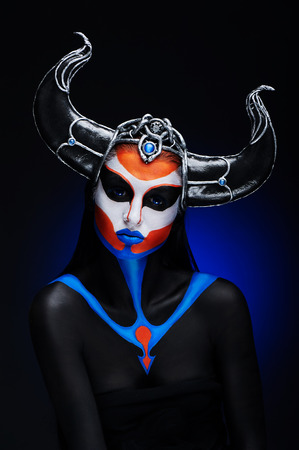 bodypainting: Mystery portrait of female faun with blue eyes, body art and silver snakes on black horns