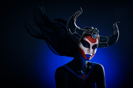 Mystery portrait of female faun with blue eyes, body art and silver snakes on black horns