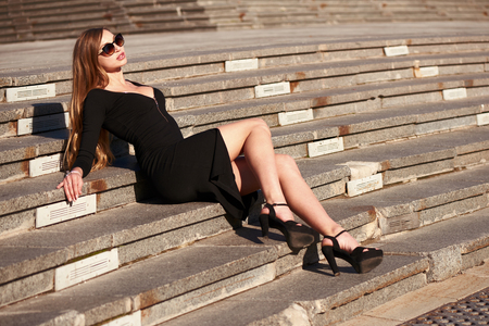 Beautiful blonde lady in black dress with decolletage posing on the staircase in early morning outdoor