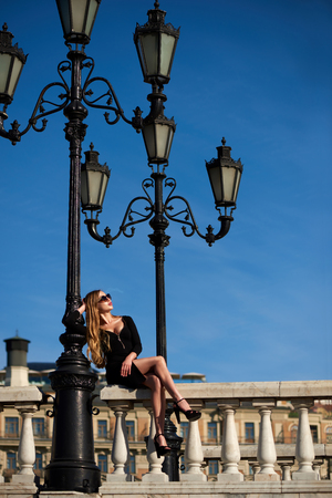 Lady in black dress sitting on baluster railing under vintage street lamp on blue sky background  Stock Photo