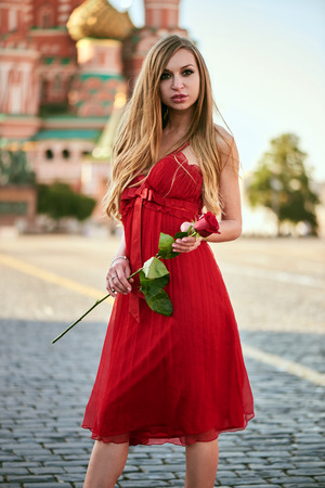 Beautiful blonde lady in red dress on Red Square in Moscow, Russia Stock Photo