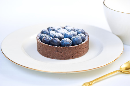 chocolaty: Hand made dessert tarlets from pistachio and chocolaty bakery dough with blueberry decoration served on plate with cap of tea