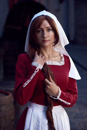 Townswoman in red dress with an apron and chaperone on the street. Costume stylized of later Middle Ages on 15 16th century.