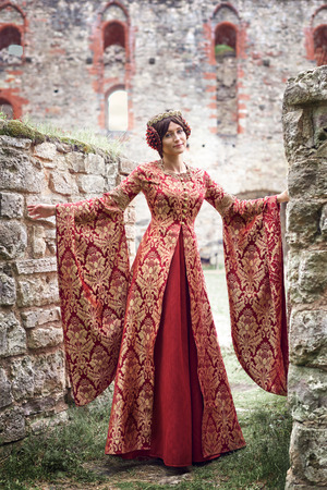 Beautiful Isabella of France, queen of England on Middle Ages period in red gown near medieval castle Stock Photo