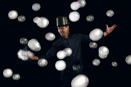 Man artist fiddle with many gel soap bubble. Soap bubble show in black studio.