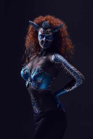 Fabulous female from fairytale with blue black body art, corset and horns