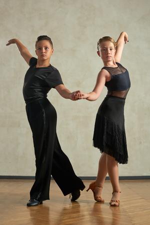 Attractive young couple of children dancing ballroom dance in studio Stock Photo