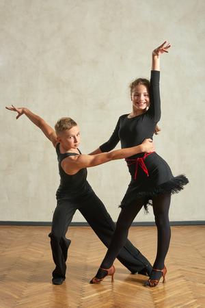 Attractive young couple of children dancing ballroom dance in studio 스톡 콘텐츠