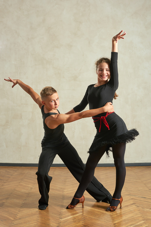 Attractive young couple of children dancing ballroom dance in studio Stok Fotoğraf