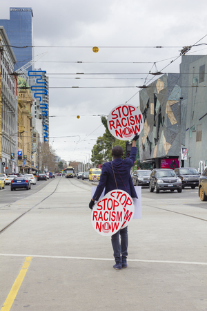 bigotry: Melbourne, Australia - July 25, 2015: View of an unidentified protester holding stop racism now placards outside the Flinders Street Station in Melbourne.