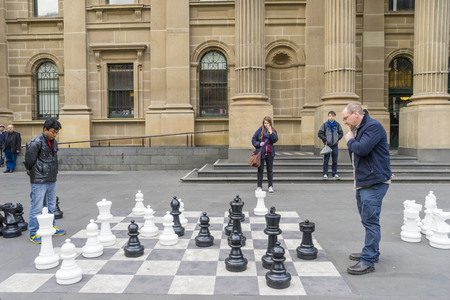 onlooker: Melbourne, Australia - August 1, 2015: Two men playing giant outdoor chess outside the State Library of Victoria in Melbourne while some people watching them.
