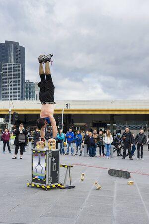 handstand: Melbourne, Australia - August 8, 2015: Street performer doing BlockDrop handstand at Federation Square in Melbourne.