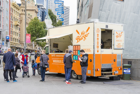 street food: Melbourne, Australia - August 8, 2015: Food truck selling hamburgers in Melbourne street with people queuing up to buy their food. Food trucks represent a new generation of dining. Editorial