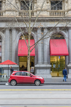 Melbourne, Australia - August 8, 2015: Red car parked outside the Lindt Chocolate Cafe in Melbourne. The cafe is one of the main tourist attractions in Melbourne. Editorial