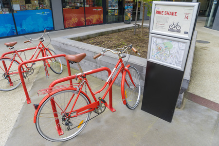 tertiary: Melbourne, Australia - August 12, 2015: Red bicycles in a docking station from the Free Bike Share Program in Melbourne for staff and students of La Trobe University to travel around Bundoora Campus. Editorial