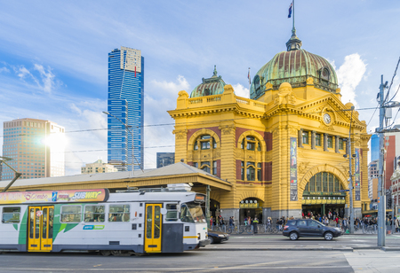 flinders: Melbourne, Australia - August 16, 2015: Flinders Street Railway Station in Melbourne with tram, Eureka Tower and other modern buildings near sunset.