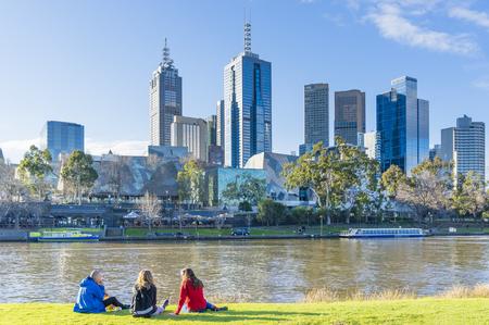 メルボルン、オーストラリア - 2015 年 8 月 15 日: 人々 は背景として都市の景観と日没近くメルボルンのヤラ川の銀行に座っています。