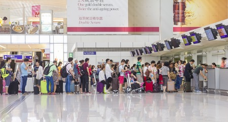Hong Kong, China - June 23, 2015: Passengers queuing up in check-in counter in the Hong Kong International Airport.