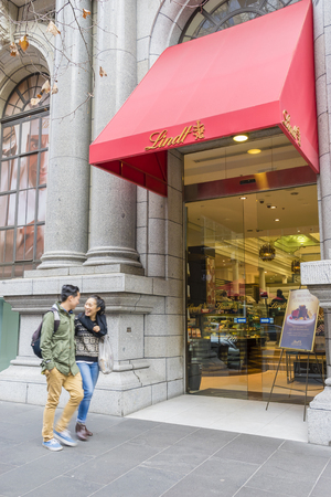 lindt: Melbourne, Australia - August 8, 2015: Couple outside the Lindt Chocolate Cafe in Melbourne. The cafe is one of the main tourist attractions in Melbourne. Editorial