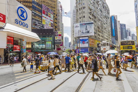 hong kong street: Hong Kong, China - June 17, 2015: Commuters crossing a street in Causeway Bay, one of the busiest districts in Hong Kong in a hot, sunny day. Editorial