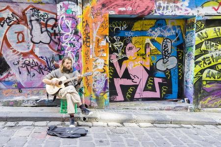 Melbourne, Australia - August 30, 2015: Street musician playing guitar in Hosier Lane in Melbourne. Hosier Lane is one of the citys best street art locations. Editorial