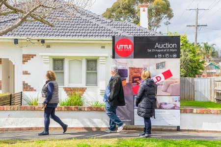 sold: Melbourne, Australia - August 30, 2015: People walking past an auction sign on display outside a house in Melbourne during daytime.