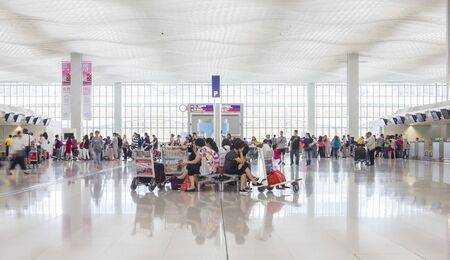 checkin: Hong Kong, China - June 23, 2015: Passengers waiting and queuing up in check-in counter in Hong Kong International Airport.