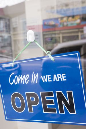 store sign: Come in we are open sign hanging on a window door outside an office or a shop