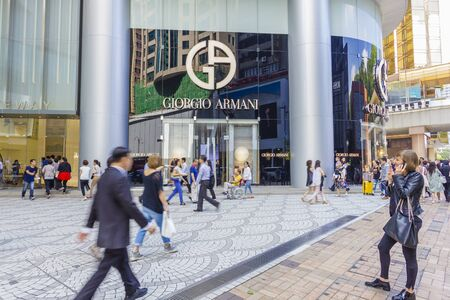 lunch hour: Hong Kong, China - June 16, 2015: Communters or shoppers walking pass the Giorgio Armani store in Hong Kong during lunch hour.