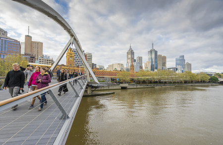 southgate: Melbourne, Australia - September 18, 2015: People walking across the Southgate footbridge in Melbourne on a cloudy day near sunset.